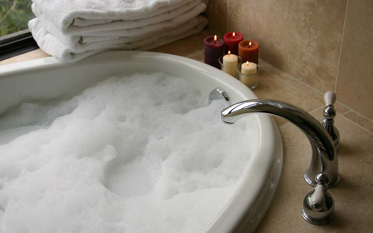 A bubble bath with lit candles beside it