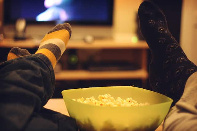 A bowl of popcorn in between 2 peoples's legs, who are lying back watching TV