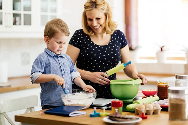 A woman and child preparing to bake something in a kitchen